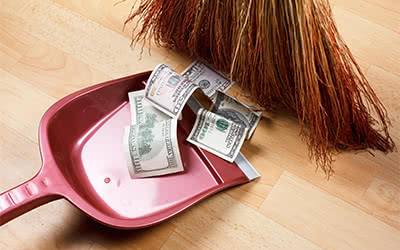 A broom sweeps money into a dustpan
