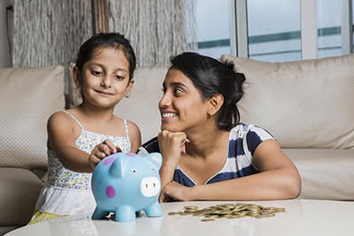 A mother smiles as her daughter puts coins into a piggy bank