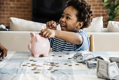 A happy child with plays with dollars and cents on a table