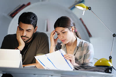 A couple looks mildly concerned while reviewing financial documents
