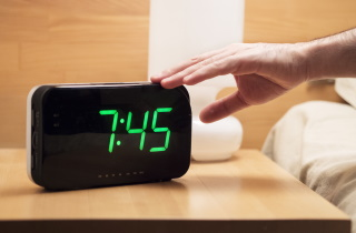 Hand on alarm clock