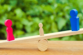 Three wood figures on seesaw