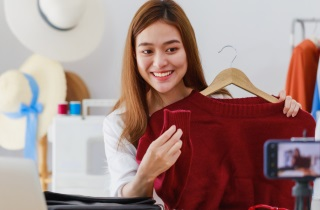 Woman blogger shows sweater to camera and laptop