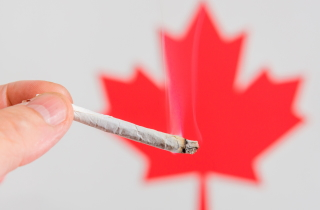 Smoldering cannabis in front of Canadian flag