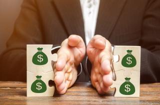 Hand dividing bags of money