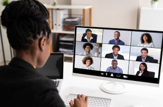 Woman sitting in front of computer, videoconferencing with a group of people on the screen.