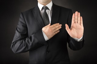 Man in suit holding one hand to heart and other hand palm out