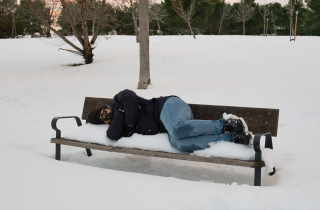Man sleeping on snowy bench