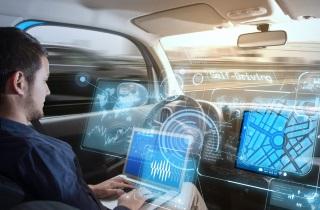 Man using laptop in self-driving car