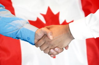Two hands shaking in front of Canadian flag