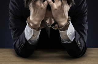 Dejected businessman wearing handcuffs