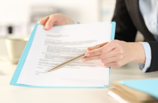 Hand with pen pointing to contract