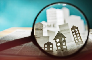 Paper houses shown in magnifying glass