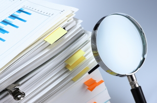 Magnifying glass and corporate files