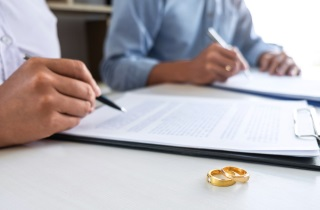 Couple signs divorce papers with wedding rings in foreground