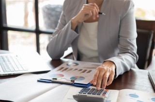 Businesswoman sitting at desk with calculator and papers