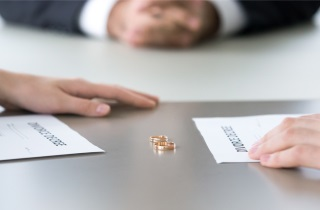 Three people sitting at table with divorce papers and wedding rings on table