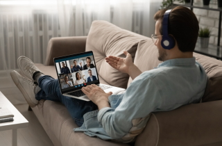 Young lawyer on couch in virtual negotiation with others