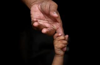 Child's hand holding senior's finger