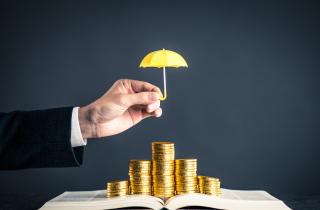 Hand shielding money with an umbrella