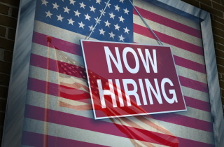 """A """"Now Hiring"""" sign in front of U.S. flag"""