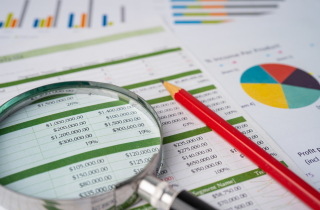 Magnifying glass looking at financial spread sheet