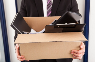 Hands holding box of personal effects of fired person