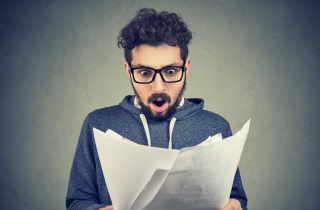Shocked man looking at resumes