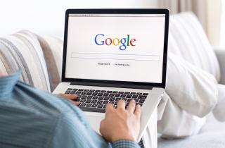 Man with laptop using Google