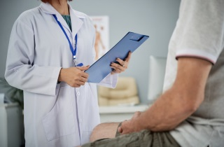 Doctor holding clipboard talks to patient