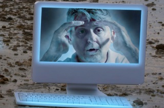 Man looking through computer screen from other side