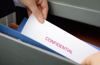 Hands pull confidential file from folder