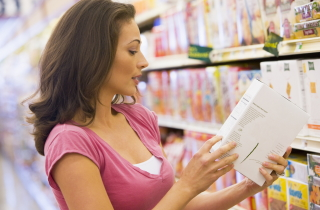 Woman in store reading label on box