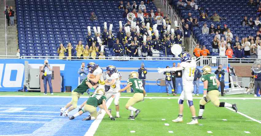 Carter Thelen is hit at the goal line during the division 7 state title game Saturday at Ford Field.