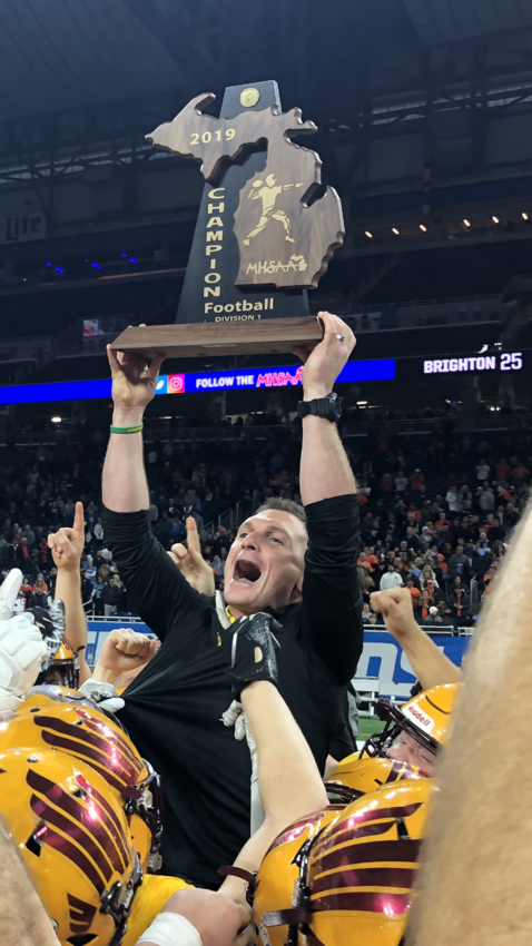 Coach Jake Weingartz celebrates Davison's first state title on the shoulders of his players Saturday at Ford Field