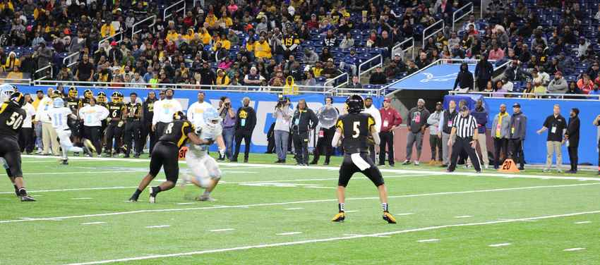 Dante Moore drops back to pass against Muskegon Mona Shores Friday at Ford Field.