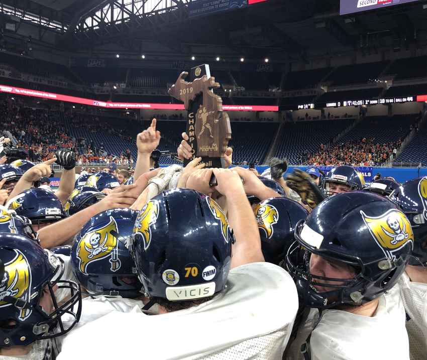 Pewamo-Westphalia celebrates with the championship trophy Saturday at Ford Field.
