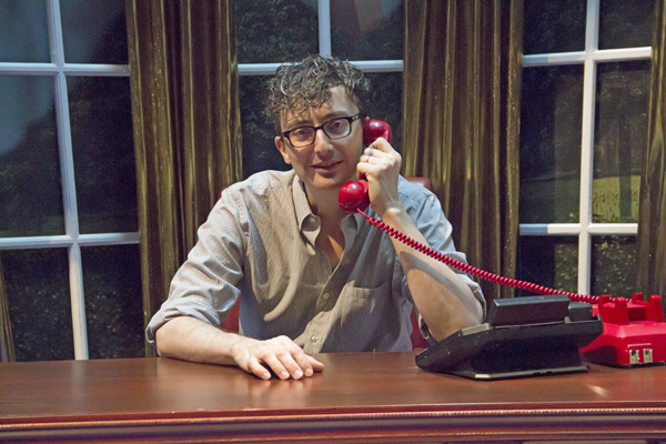 Beowulf Boritt takes a very important call at the president's desk in Clinton the Musical, directed by Dan Knechtges, at New World Stages.