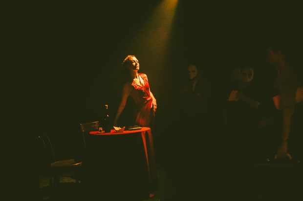 Hecate (Isadora Wolfe) rises from her table in Sleep No More.