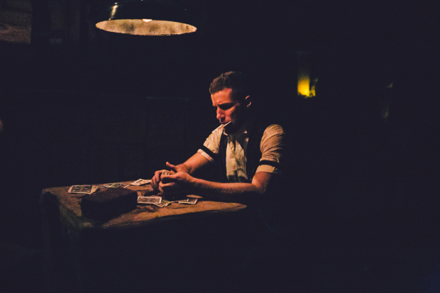 A lonely card game takes place in Sleep No More, directed by Felix Barrett and Maxine Doyle, at the McKittrick Hotel.
