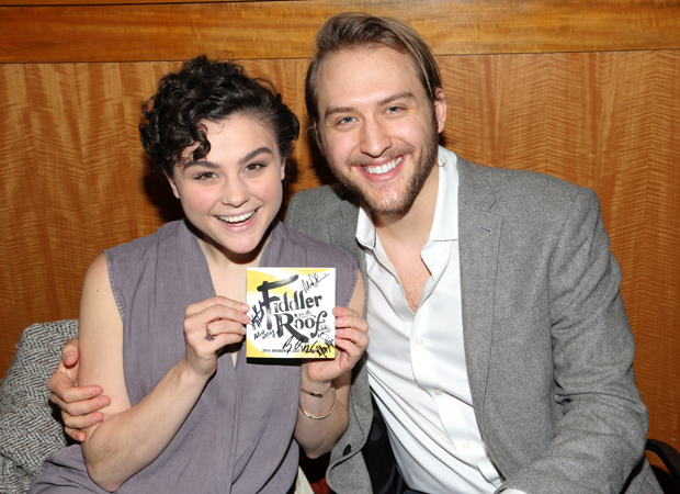 Melanie Moore And Nick Rehberger Pose With A Signed Copy Of The Fiddler On  The Roof