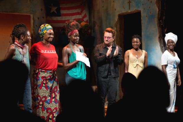 Lupita Nyong'o reads a speech as her costars and Bono look on.
