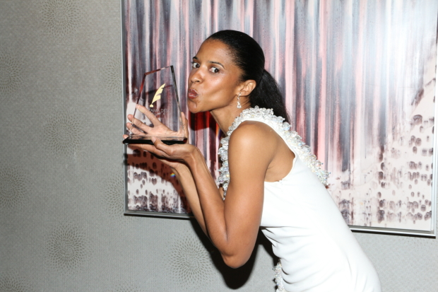 Hamilton star Renée Elise Goldsberry kisses her 2015 Drama Desk Award.
