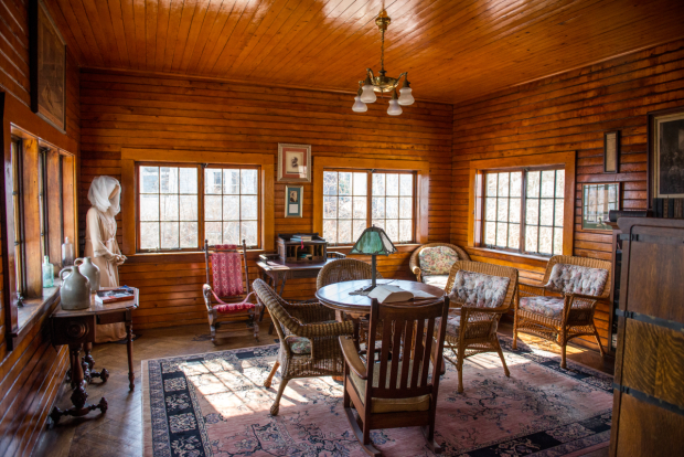 Monte Cristo Cottage's living room inspired O'Neill with the setting for his most intimate play. The room is, in fact, a converted schoolhouse. In the back-left corner can be seen a costume worn by Colleen Dewhurst in the 1988 Yale Rep centennial production of Long Days Journey Into Night.
