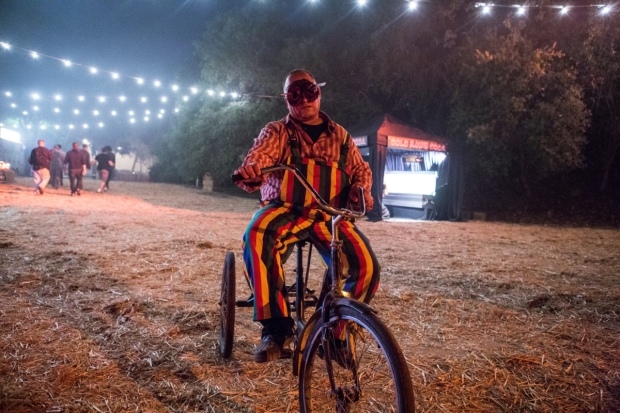 A creepy clown rides a tricycle at the New York Haunted Hayride.