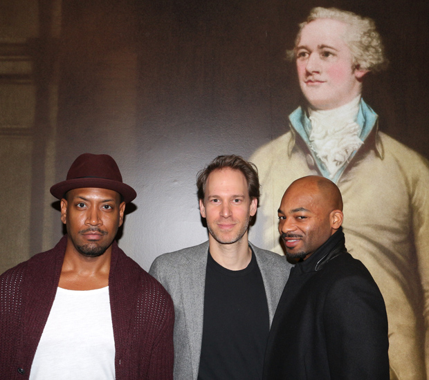 Hamilton family members Bryan Terrell Clark (George Washington), David Korins (set designer), and Brandon Victor Dixon (Aaron Burr) pose with a photograph of Alexander Hamilton at Sotheby's.