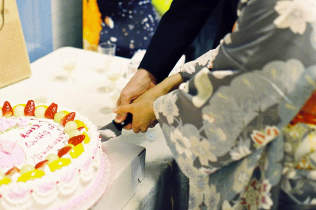 Minami Yusui and Dan Urness cut their wedding cake.