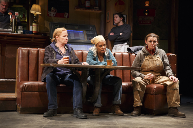 Tracey (Johanna Day), Cynthia (Michelle Wilson), and Jessie (Alison Wright) enjoy a beer as Stan (James Colby) tends bar and Oscar (Carlo Albán) cleans up in Sweat on Broadway.