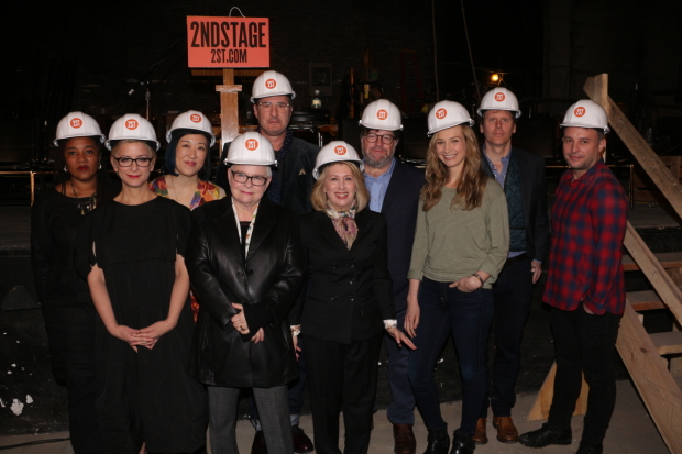 Lynn Nottage, Anna D. Shapiro, Young Jean Lee, Paula Vogel, Jon Robin Baitz, Carole Rothman, Kenneth Lonergan, Bess Wohl, Will Eno, and Trip Cullman pose in hardhats at the Helen Hayes Theatre.