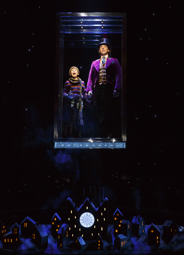 Charlie (Jake Ryan Flynn) and Willy Wonka (Christian Borle) ride in a great glass elevator in the final scene of Charlie and the Chocolate Factory on Broadway.